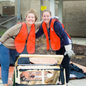 Two student volunteers take a break from disassembling a futon to pose for a photo during move out