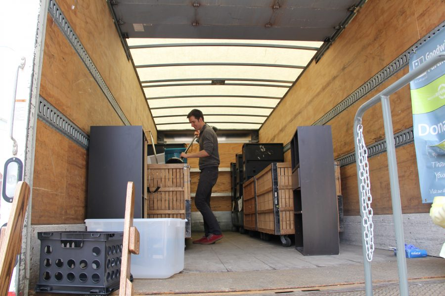 Student places items in a moving truck during move-out.