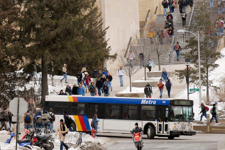 Pedestrian walk along a Madison Metro Bus.