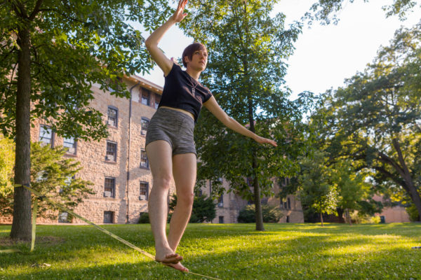 A woman attempts to keep her balance on a slackfline outside Tripp Residence Hall