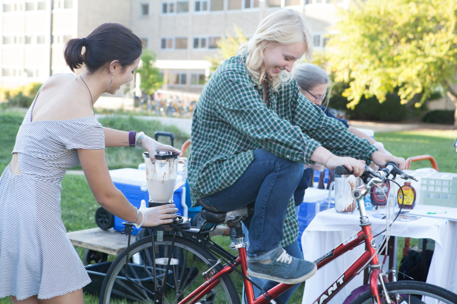 Students using bike-powered blenders to make an ice cream shake at Sustain-a-Bash