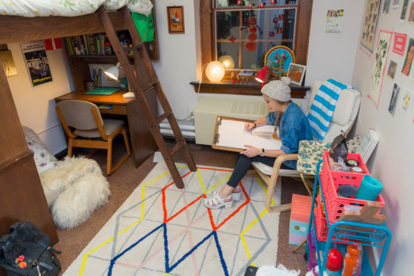 A student does art homework in her Tripp Residence Hall room