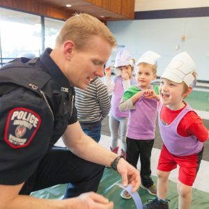 Officer Evans helps a little one with their police hat at a KIDSville event.